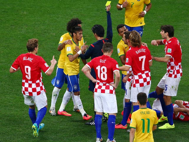 Neymar of Brazil is shown a yellow card by referee Yuichi Nishimura during the 2014 FIFA World Cup Brazil Group A match between Brazil and Croatia at Arena de Sao Paulo on June 12, 2014