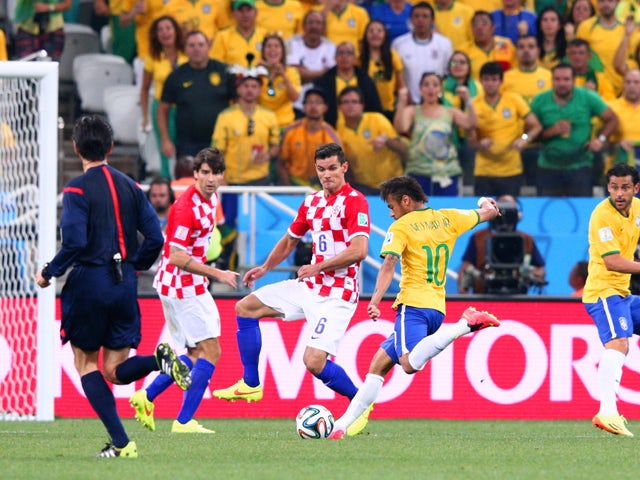 Neymar of Brazil shoots and scores against Dejan Lovren of Croatia in the first half during the 2014 FIFA World Cup Brazil Group A match between Brazil and Croatia at Arena de Sao Paulo on June 12, 2014
