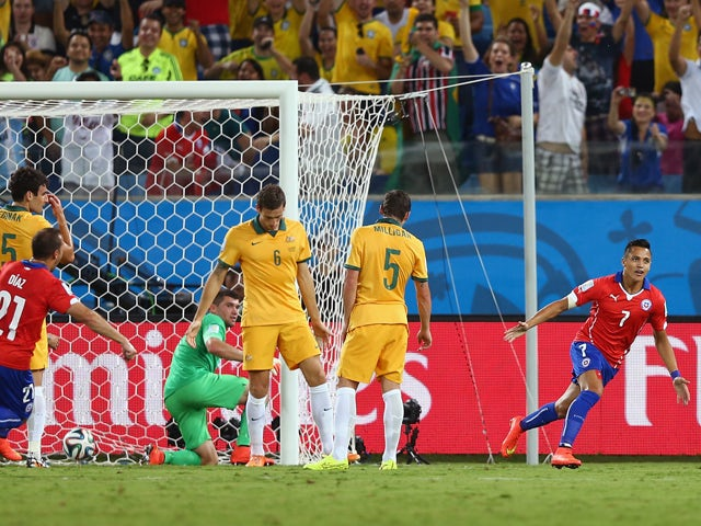 Alexis Sanchez of Chile celebrates after scoring his teams first goal against goalkeeper Mathew Ryan of Australia during the 2014 FIFA World Cup Brazil Group B match between Chile and Australia at Arena Pantanal on June 13, 2014