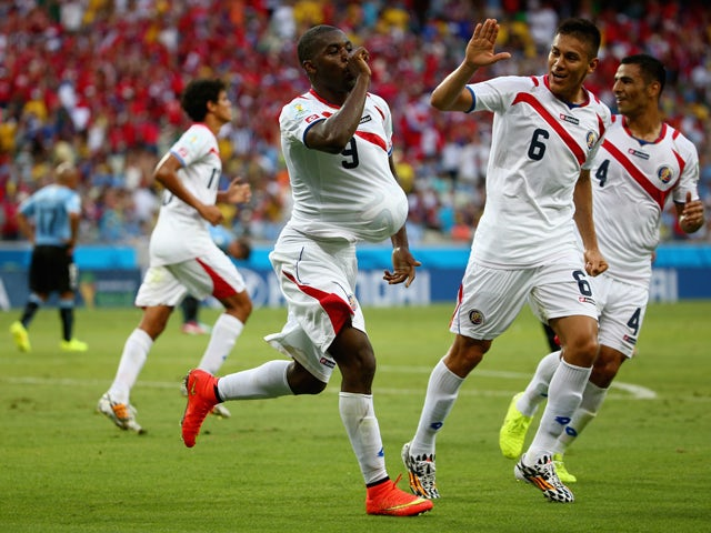 Joel Campbell of Costa Rica celebrates scoring his team's first goal with the ball under his jersey as teammates Oscar Duarte and Michael Umana run on during the 2014 FIFA World Cup Brazil Group D match between Uruguay and Costa Rica at Castelao on June 1