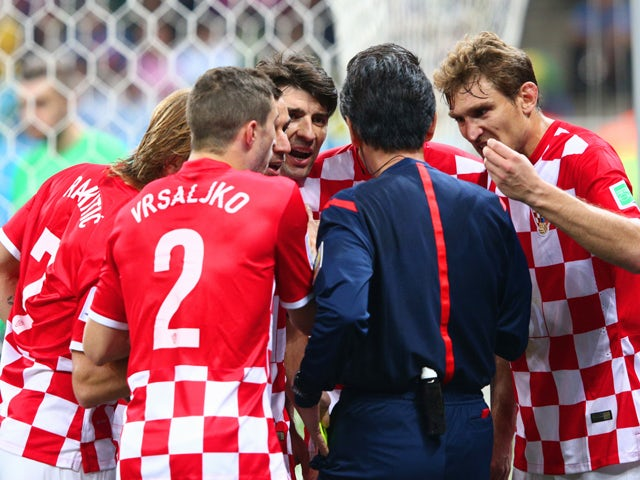Referee Yuichi Nishimura is surrounded by Croatia players after awarding a penalty kick in the second half during the 2014 FIFA World Cup Brazil Group A match between Brazil and Croatia at Arena de Sao Paulo on June 12, 201