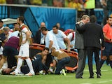 England manager Roy Hodgson speaks to head coach Cesare Prandelli of Italy as England trainer Gary Lewin lies on the ground being treated for an injury during the 2014 FIFA World Cup Brazil Group D match between England and Italy at Arena Amazonia on June