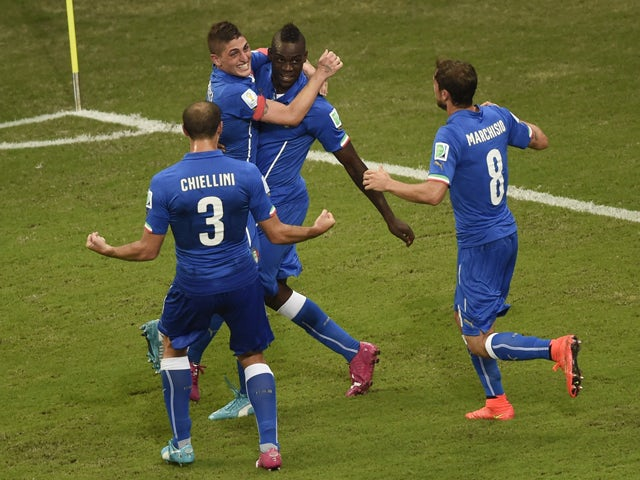 Italy's forward Mario Balotelli celebrates with teammates after scoring during a Group D football match between England and Italy at the Amazonia Arena in Manaus during the 2014 FIFA World Cup on June 14, 2014