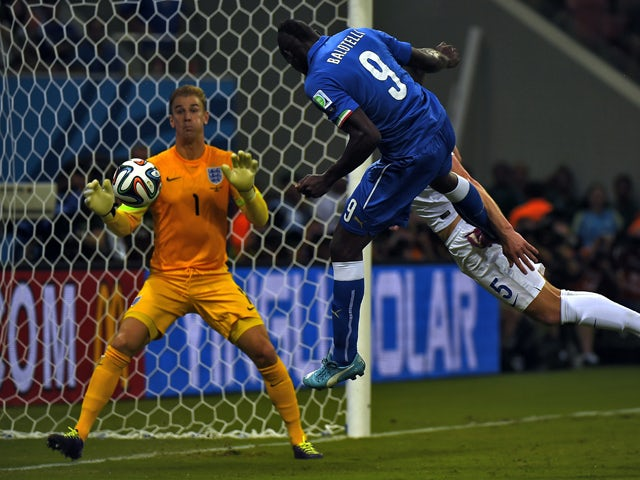 Italy's forward Mario Balotelli heads the ball to score a goal as England's goalkeeper Joe Hart (L) and England's defender Gary Cahill try to defend during a Group D football match between England and Italy at the Amazonia Arena in Manaus during the 2014