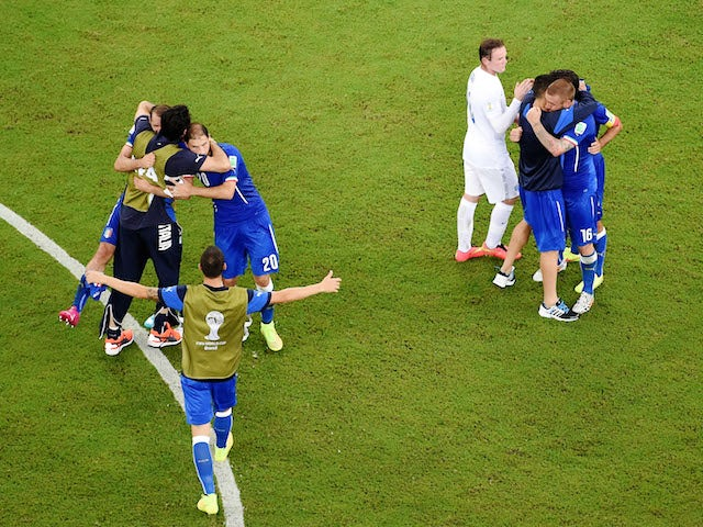 Wayne Rooney of England congratulates Italy as they celebrate their win during the 2014 FIFA World Cup Brazil Group D match at Arena Amazonia on June 14, 2014
