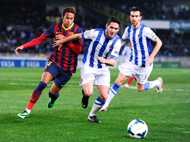 Neymar of FC Barcelona duels for the ball with Joseba Zaldua of Real Sociedad during the La Liga match between Real Sociedad and FC Barcelona at Estadio Anoeta on February 22, 2014