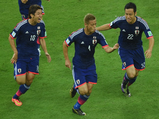 :Japan's forward Keisuke Honda celebrates after scoring during a Group C football match between Ivory Coast and Japan at the Pernambuco Arena in Recife during the 2014 FIFA World Cup on June 14, 2014