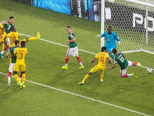 Giovani dos Santos of Mexico puts the ball in the net but the goal was disallowed due to an offsides call as Charles Itandje of Cameroon looks on in the first half during the 2014 FIFA World Cup Brazil Group A match between Mexico and Cameroon at Estadio