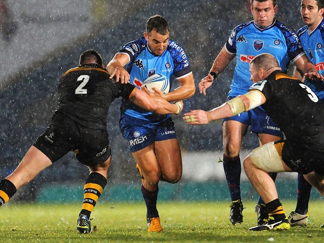 Ollie Barkley of Grenoble is tackled by Tom Lindsay and Jake Cooper-Woolley of London Wasps during the Amlin Challenge Cup match between London Wasps and Grenoble at Adams Park on December 15, 2013