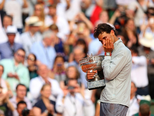 Rafael Nadal of Spain wipes tears away from his eyes as he celebrates with the Coupe de Mousquetaires after victory in his men's singles final match against Novak Djokovic at the French Open on June 8, 2014
