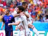 Jordi Alba of Spain jumps on teammate Xabi Alonso in celebration after a goal on a penalty kick by Alonso in the first half during the 2014 FIFA World Cup Brazil Group B match between Spain and Netherlands at Arena Fonte Nova on June 13, 2014
