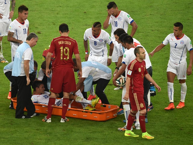 Chile's midfielder Jose Pedro Fuenzalida is taken off the pitch in a stretcher during a Group B football match between Spain and Chile in the Maracana Stadium in Rio de Janeiro during the 2014 FIFA World Cup on June 18, 2014