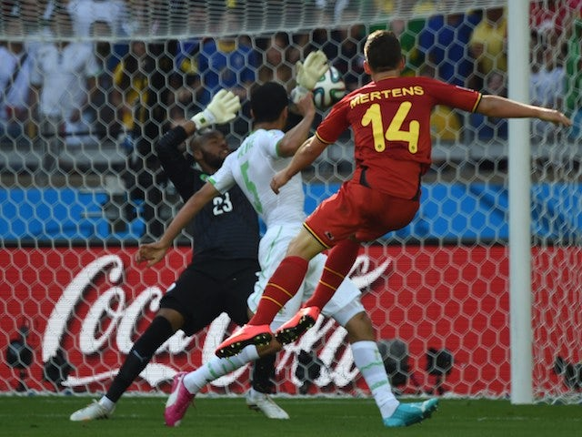 Belgium's forward Dries Mertens (R) scores against Algeria's goalkeeper Rais Mbohli (L) as Algeria's defender Rafik Halliche (C) looks on during a Group H football match on June 17, 2014