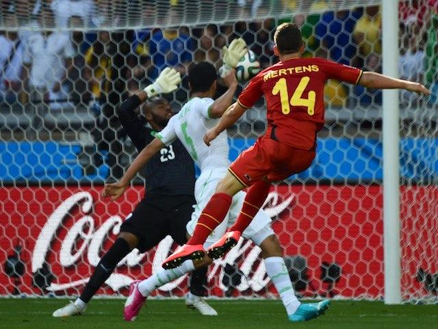 Belgium's forward Dries Mertens (R) scores against Algeria's goalkeeper Rais Mbohli (L) as Algeria's defender Rafik Halliche (C) looks on during a Group H football match on June 17, 2014