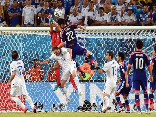 Japan's goalkeeper Eiji Kawashima (L) and Japan's defender Maya Yoshida (C) jump for the ball during a Group C football match on June 19, 2014