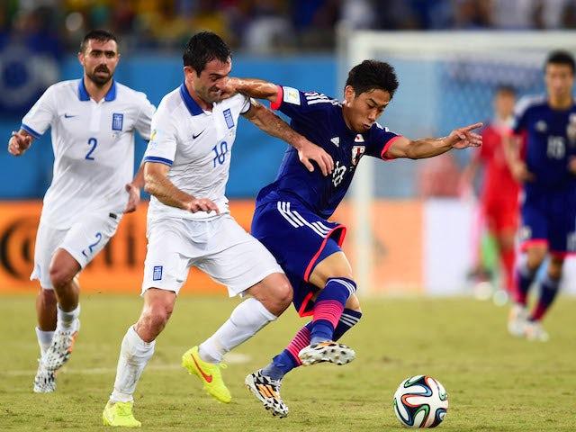 Giorgos Karagounis of Greece challenges Shinji Kagawa of Japan during the 2014 FIFA World Cup Brazil Group C match between Japan and Greece at Estadio das Dunas on June 19, 2014