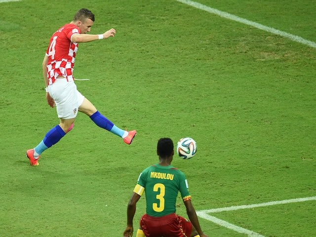 Croatia's midfielder Ivan Perisic (L) kicks to score as Cameroon's defender Nicolas Nkoulou looks on during a Group A football match on June 19, 2014