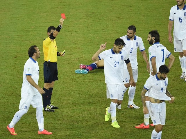Greece's midfielder Kostas Katsouranis (5th R) is given the red card following a foul on Japan's midfielder Makoto Hasebe during a Group C match on June 20, 2014