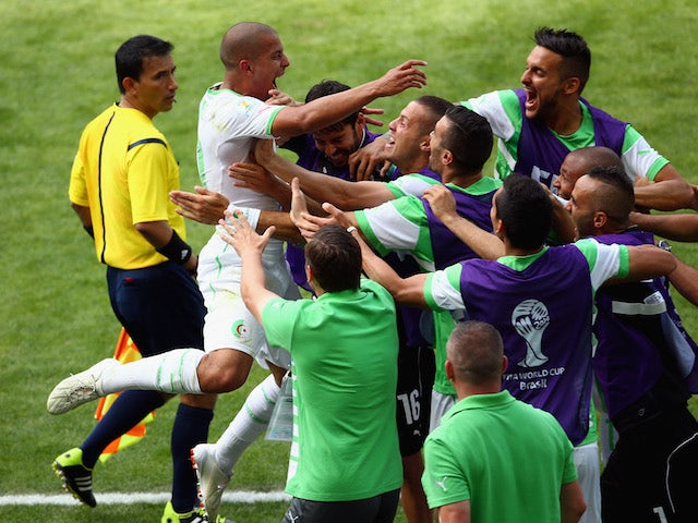 Sofiane Feghouli of Algeria celebrates with his teammates after scoring a penalty during the World Cup Group H match against Belgium in Belo Horizonte on June 17, 2014