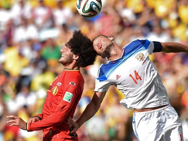 Russia's defender Vasily Berezutsky (R) heads wht ball past Belgium's midfielder Marouane Fellaini during the Group H football match on June 22, 2014