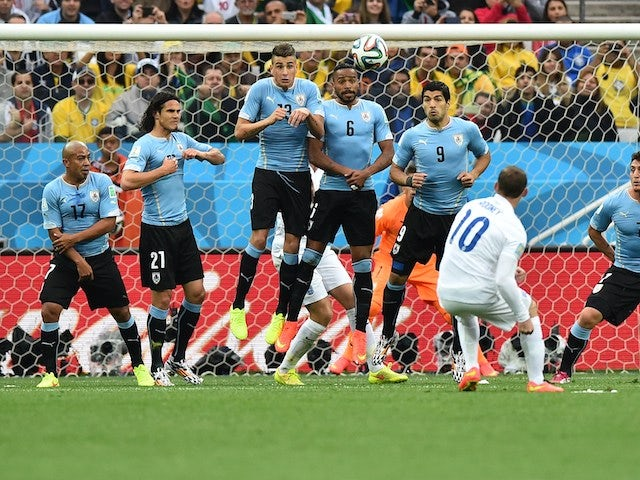 England's forward Wayne Rooney (2R) takes a free-kick past Uruguayan defenders during the Group D football match between Uruguay and England at the Corinthians Arena in Sao Paulo on June 19, 2014