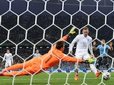 England's forward Wayne Rooney (L) scores against Uruguay's goalkeeper Fernando Muslera (L) during a Group D football match on June 19, 2014