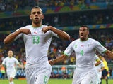 Islam Slimani of Algeria celebrates scoring his team's first goal with Essaid Belkalem during the 2014 FIFA World Cup Brazil Group H match between Algeria and Russia at Arena da Baixada on June 26, 2014