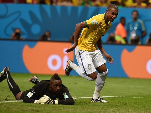 Brazil's midfielder Fernandinho celebrates after scoring their fourth goal as Cameroon's goalkeeper Charles Itandje reacts during the Group A football match between Cameroon and Brazil at the Mane Garrincha National Stadium in Brasilia during the 2014 FIF