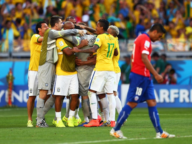 Julio Cesar of Brazil celebrates with teammates after defeating Chile in a penalty shootout during the 2014 FIFA World Cup Brazil round of 16 match between Brazil and Chile at Estadio Mineirao on June 28, 2014