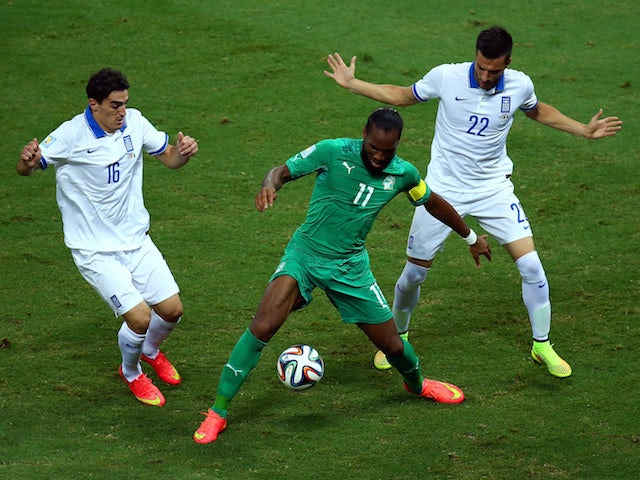 Didier Drogba of the Ivory Coast is challenged by Lazaros Christodoulopoulos (L) and Andreas Samaris of Greece during the 2014 FIFA World Cup Brazil Group C match on June 24, 2014