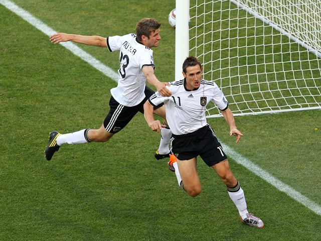 Miroslav Klose of Germany celebrates scoring the opening goal with team mate Thomas Muller during the 2010 FIFA World Cup South Africa Round of Sixteen match between Germany and England at Free State Stadium on June 27, 2010