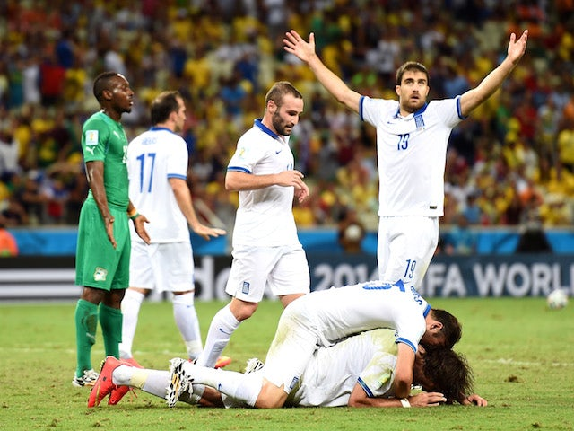 Giorgos Samaras of Greece celebrates with teammates after scoring his team's second goal on a penalty kick during the 2014 FIFA World Cup Brazil Group C match on June 24, 2014