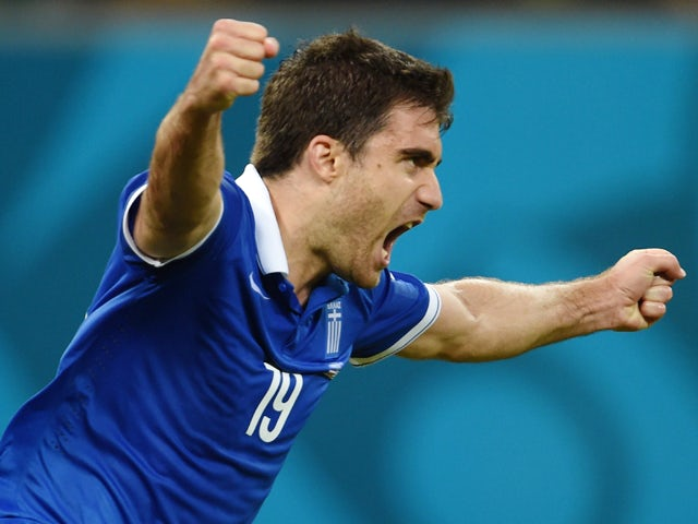 Greece's defender Sokratis Papastathopoulos celebrates after scoring during a Round of 16 football match between Costa Rica and Greece at Pernambuco Arena in Recife during the 2014 FIFA World Cup on June 29, 2014