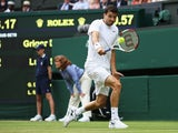 Grigor Dimitrov of Bulgaria plays a backhand shot during his Gentlemen's Singles second round match against Luke Saville of Australia on day three of the Wimbledon Lawn Tennis Championships at the All England Lawn Tennis and Croquet Club at Wimbledon on J