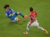Mexico's goalkeeper Guillermo Ochoa (L) defends against Croatia's forward Mario Mandzukic (R) during a Group A football match on June 23, 2014