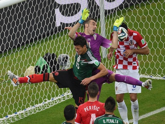 Mexico's defender Hector Moreno and Croatia's goalkeeper Stipe Pletikosa clash during a Group A football match on June 23, 2014