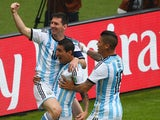 Lionel Messi celebrates with Argentina teammates Angel Di Maria and Marcos Rojo after opening the scoring against Nigeria in their World Cup Group F match on June 25, 2014