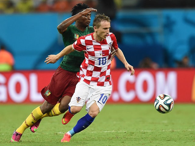 Croatia's midfielder Luka Modric is tackled by Cameroon's forward Benjamin Moukandjo during the Group A football match between Cameroon and Croatia at The Amazonia Arena in Manaus on June 18, 2014