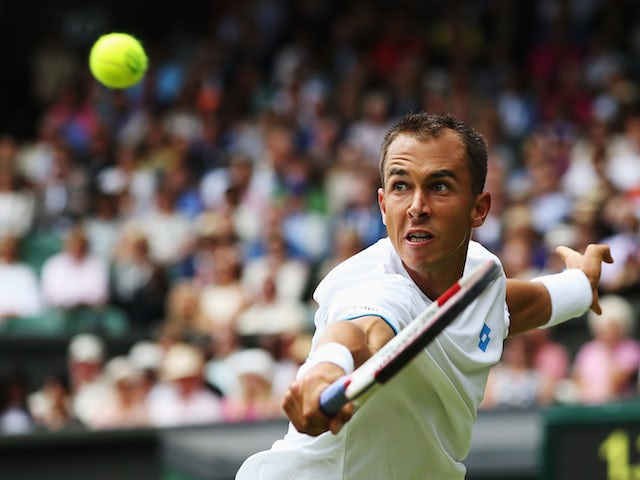 Lukas Rosol of Czech Republic hits a backhand return during his Gentlemen's Singles second round match against Rafael Nadal on June 26, 2014