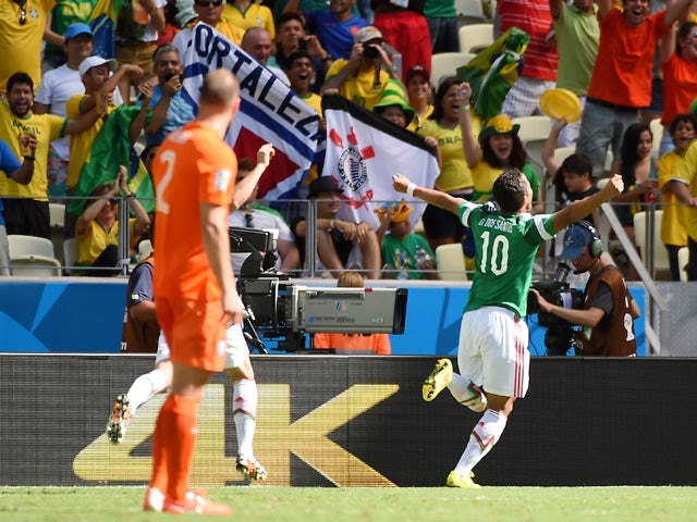 Mexico's forward Giovani Dos Santos is watched by Netherlands' defender Ron Vlaar as he celebrates with teammates after scoring during a Round of 16 football match between Netherlands and Mexico at Castelao Stadium in Fortaleza during the 2014 FIFA World