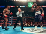 Referee Lane Mills stops the fight in the third round as Evander Holyfield holds his ear as Mike Tyson watches 28 June, 1997