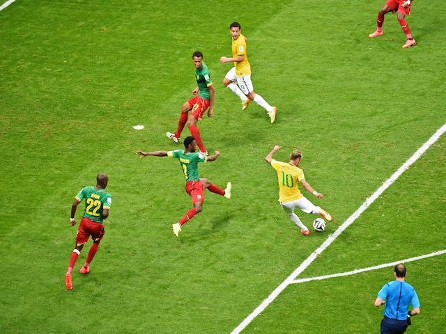 Brazil's forward Neymar (C) strikes the ball to score a second goal during the Group A football match against Cameroon on June 23, 2014