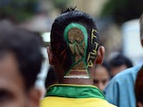 India football enthusiast Nilesh Kadam sports a FIFA World Cup trophy logo painted into a haircut as he walks along a street after visiting a salon in Mumbai on June 9, 2014