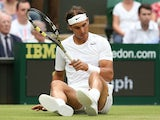 Spain's Rafael Nadal sits on the grass after slipping against Kazakhstan's Mikhail Kukushkin during their men's singles third round match on June 28, 2014