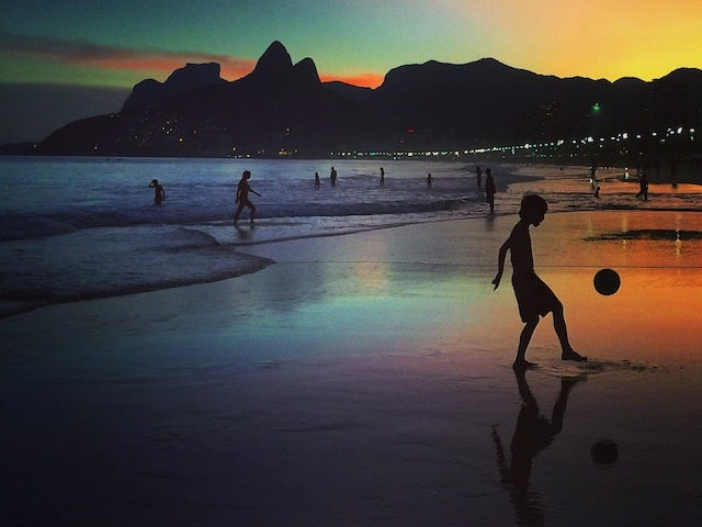 A young boy plays football at sunset on June 8, 2014 in Rio de Janeiro, Brazi
