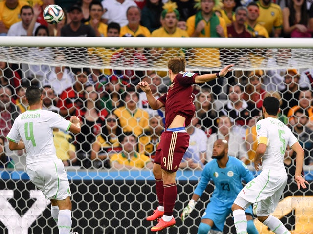 Russia's forward Alexander Kokorin scores his team's first goal past Algeria's goalkeeper Rais Mbohli during a Group H football match between Algeria and Russia at the Baixada Arena in Curitiba during the 2014 FIFA World Cup on June 26, 2014