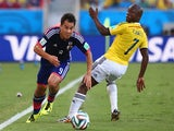 Shinji Okazaki of Japan driblbles past Pablo Armero of Colombia during the 2014 FIFA World Cup Brazil Group C match between Japan and Colombia at Arena Pantanal on June 24, 2014
