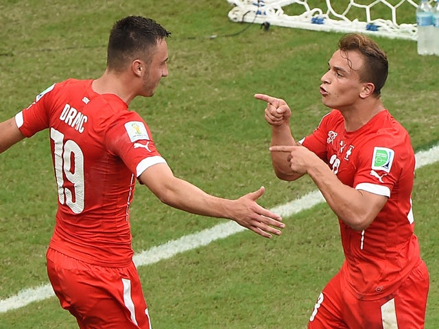 Switzerland's midfielder Xherdan Shaqiri celebrates with forward Josip Drmic (L) after scoring his team's second goal during the Group E football match between Honduras and Switzerland at the Amazonia Arena in Manaus during the 2014 FIFA World Cup on June
