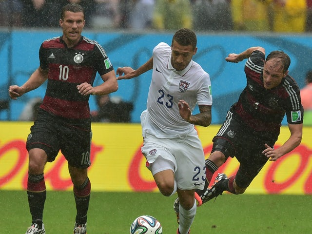 Germany's forward Lukas Podolski and Germany's defender Benedikt Howedes vie for the ball with US defender Fabian Johnson during a Group G football match between US and Germany at the Pernambuco Arena in Recife during the 2014 FIFA World Cup on June 26, 2