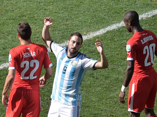 Argentina's forward Gonzalo Higuain reacts between Switzerland's defender Fabian Schaer and Switzerland's defender Johan Djourou during the second half of a Round of 16 football match between Argentina and Switzerland at Corinthians Arena in Sao Paulo dur